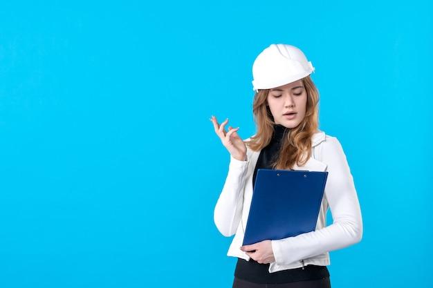 Vorderansicht junge architektin im helm auf blau