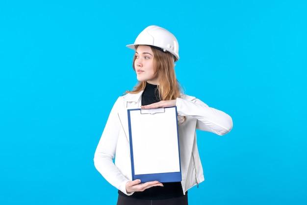 Vorderansicht junge architektin mit dateinotiz auf dem blau