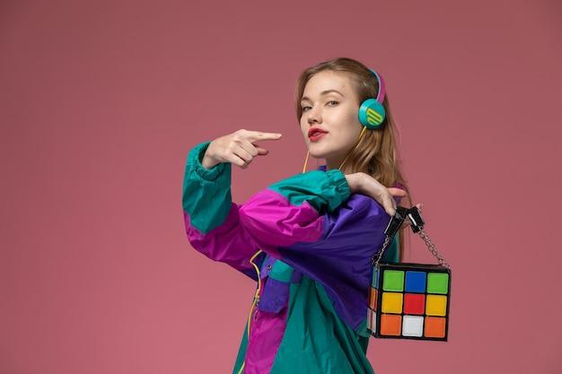 Vorderansicht junge attraktive frau, die farbigen mantel trägt, der musik auf dem dunkelrosa wandmodellfarbe weibliches junges mädchen hört