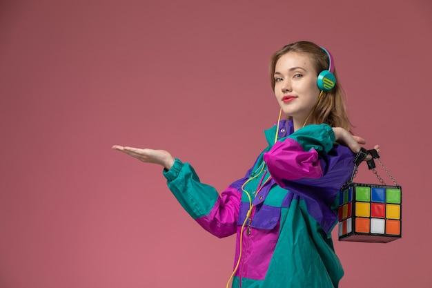 Vorderansicht junge attraktive frau, die farbigen mantel trägt, der musik mit leichtem lächeln auf dunkelrosa wandmodellfarbe weibliches junges mädchen hört