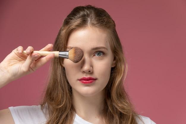 Vorderansicht junge attraktive frau, die make-up hält pinsel auf der rosa wandmodellfarbe weiblich jung macht