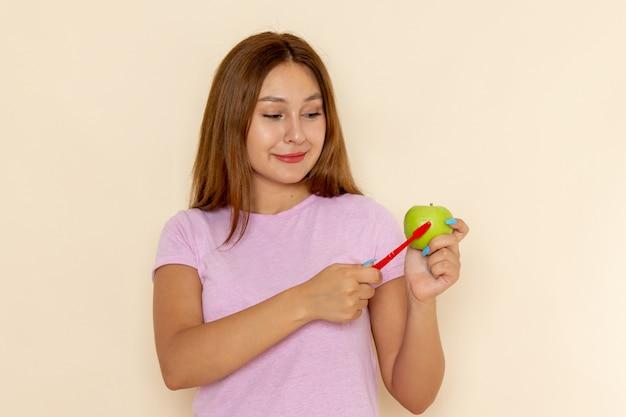 Vorderansicht junge attraktive frau im rosa t-shirt und in den blauen jeans, die grünen apfel mit zahnbürste reinigen