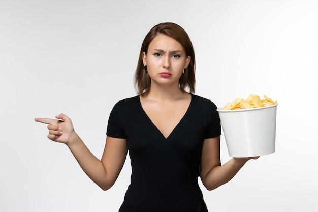Vorderansicht junge attraktive frau im schwarzen hemd, das kartoffelspitzen auf weißer oberfläche hält