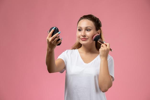 Vorderansicht junge attraktive frau im weißen t-shirt, das ein make-up mit einem leichten lächeln auf dem rosa hintergrund tut