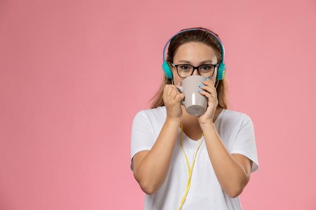 Vorderansicht junge attraktive frau im weißen t-shirt farbigen mantel, der musik hört und einen tee auf dem rosa hintergrund trinkt