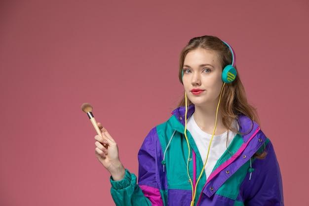 Vorderansicht junge attraktive frau im weißen t-shirt farbigen mantel posiert hörend musik halten pinsel auf dem rosa wandmodell weibliche pose farbfoto