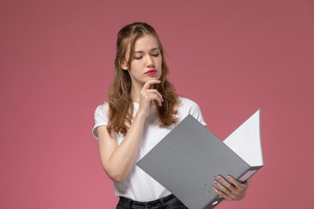 Vorderansicht junge attraktive frau in weißem t-shirt, das graues dokument hält, das es auf der weiblichen wandfarbe der weiblichen weiblichen farbe des rosa wandmodells liest