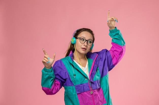 Vorderansicht junge attraktive frau in weißem t-shirt farbigem mantel und musikhören auf rosa hintergrund tanzen