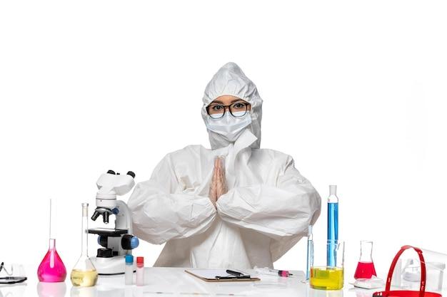 Vorderansicht junge chemikerin im speziellen schutzanzug vor tisch mit lösungen auf weißem hintergrund viruslabor covid gesundheitschemie sitzen