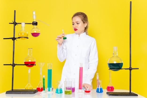 Vorderansicht junge chemikerin im weißen anzug vor dem tisch mit ed-lösungen, die einen auf den gelben raumchemie-wissenschaftsexperimenten halten