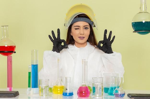 Vorderansicht junge chemikerin in speziellem schutzanzug, der mit lösungen auf hellgrünem wandchemiechemiejobwissenschaftlabor arbeitet