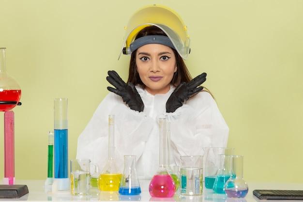 Vorderansicht junge chemikerin in speziellem schutzanzug vor tisch mit lösungen auf grüner wand job chemielabor chemie weibliche wissenschaft sitzen