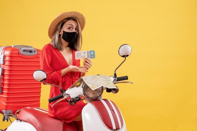 Vorderansicht junge dame auf moped mit rotem koffer, der auf ticket zeigt