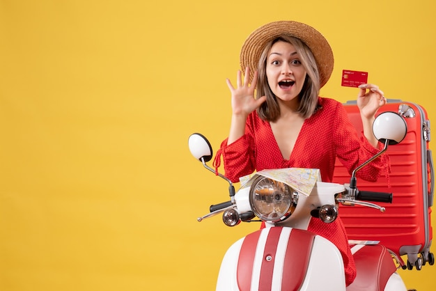 Vorderansicht junge dame im roten kleid mit kreditkarte winkende hand in der nähe von moped