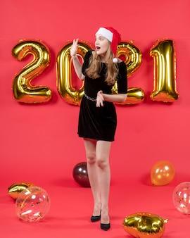 Vorderansicht junge dame im schwarzen kleid, die jemanden begrüßt, ballons auf rot