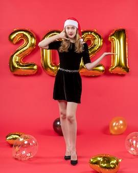 Vorderansicht junge dame im schwarzen kleid, die mich anrufen telefonzeichen ballons auf rot