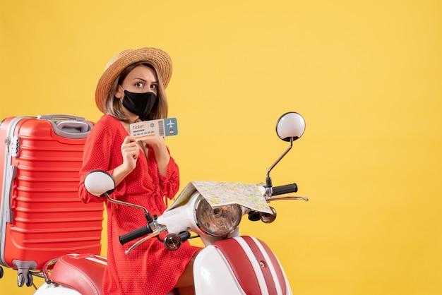 Vorderansicht junge dame mit schwarzer maske auf moped, die ticket hochhält
