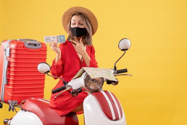 Vorderansicht junge dame mit schwarzer maske auf moped mit rotem koffer, der auf ticket zeigt