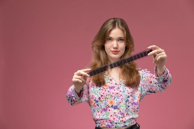 Vorderansicht junge dame zeigt filmstreifen
