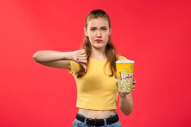 Vorderansicht junge frau am kino hält popcorn-paket und zeigt im gegensatz zu zeichen auf roten wand filme theater kino snack spaß film