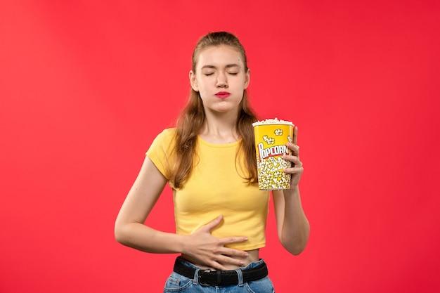 Vorderansicht junge frau am kino hält popcorn und berührt ihren bauch auf roten wand kino kino snack spaß film