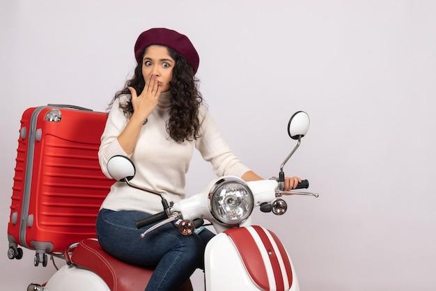 Vorderansicht junge frau auf fahrrad mit ihrer tasche auf dem weißen hintergrund farbe fahrt straßengeschwindigkeit urlaub fahrzeug motorrad