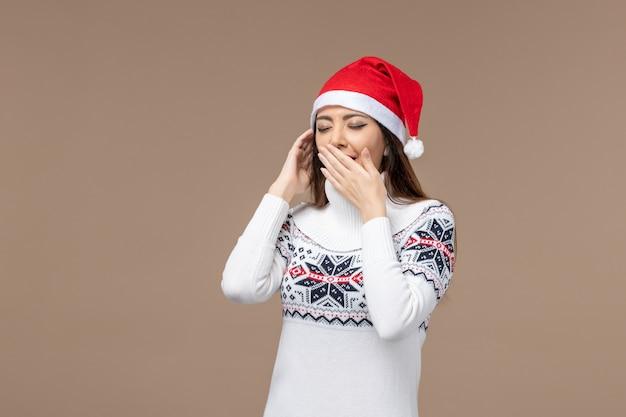 Vorderansicht junge frau, die auf braunem hintergrundweihnachtsgefühl neujahr gähnt