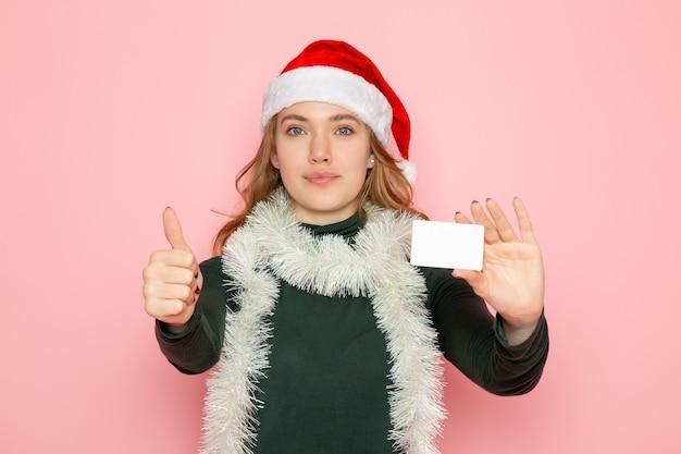 Vorderansicht junge frau, die bankkarte auf rosa wandfarbe modellferien weihnachten neujahr emotion hält