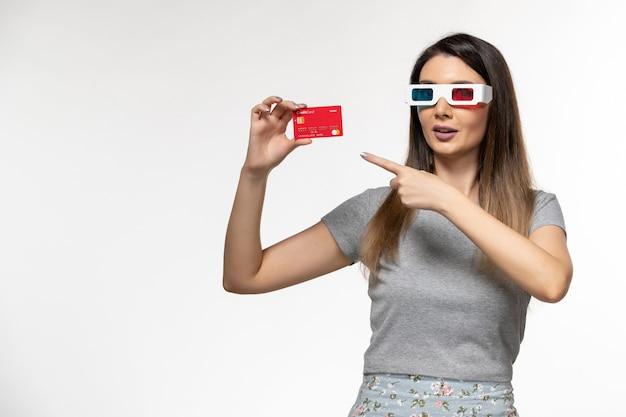 Vorderansicht junge frau, die bankkarte in d sonnenbrille auf hellweißer oberfläche hält