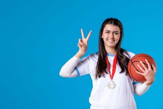 Vorderansicht junge frau, die basketball auf blauer wand hält