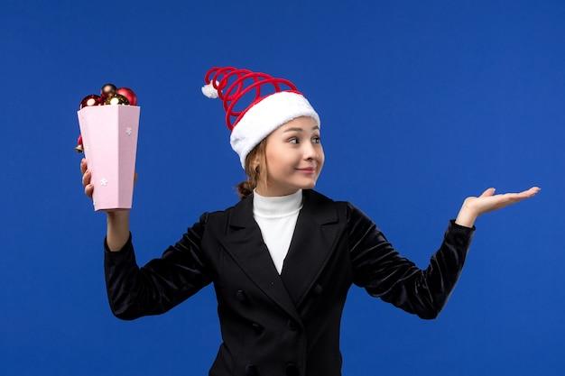 Vorderansicht junge frau, die baumspielzeug auf blauem hintergrund neujahrsfeiertagsfrauenfarbe hält