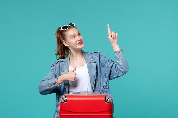 Vorderansicht junge frau, die bereit für reise ist, die auf blauem raum aufwirft