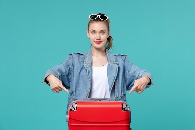 Vorderansicht junge frau, die bereit für reise mit ihrer roten tasche auf dem blauen schreibtisch ist