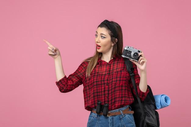 Vorderansicht junge frau, die bild mit kamera auf hellrosa hintergrundfrau fotomodell macht