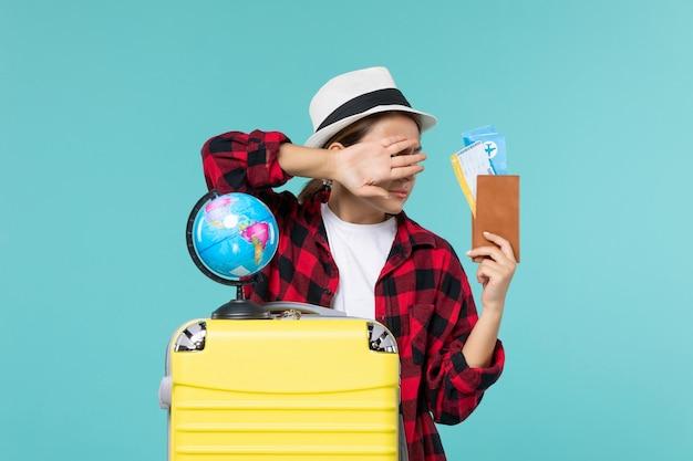 Vorderansicht junge frau, die brieftasche mit eintrittskarten hält und sich auf blauem raum versteckt