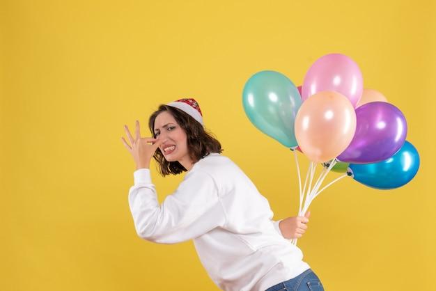 Vorderansicht junge frau, die bunte luftballons auf einem gelben hintergrund neujahrsweihnachtsfarbfeiertagsfrauenemotion versteckt