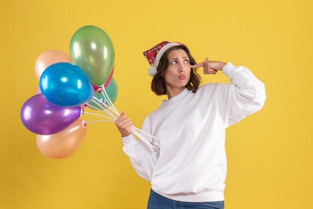 Vorderansicht junge frau, die bunte luftballons auf gelb hält