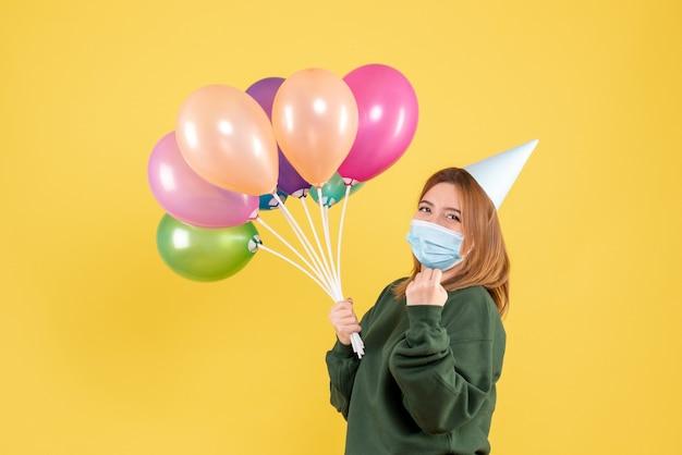 Vorderansicht junge frau, die bunte luftballons hält