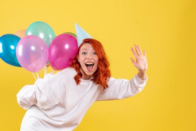 Vorderansicht junge frau, die bunte luftballons hinter ihrem rücken versteckt