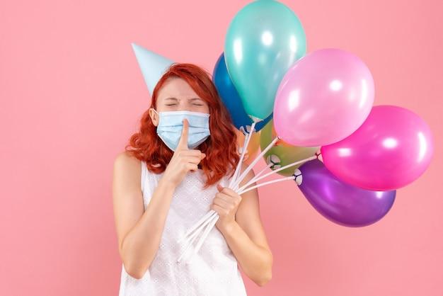Vorderansicht junge frau, die bunte luftballons in der maske auf hellrosa hält