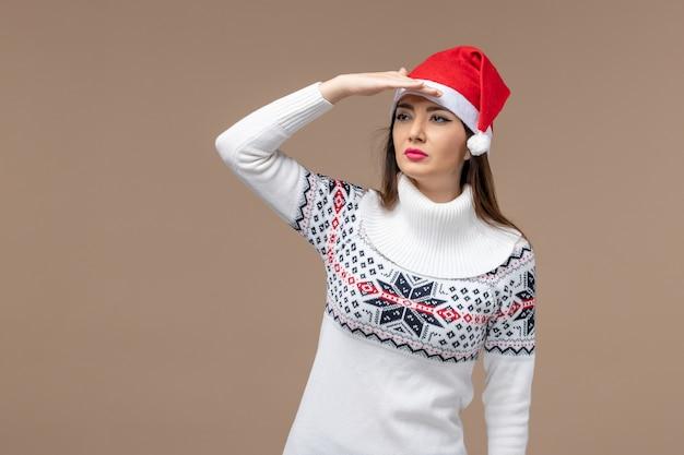 Vorderansicht junge frau, die entfernung auf dem weihnachtsfeiertagsgefühl des braunen hintergrunds betrachtet