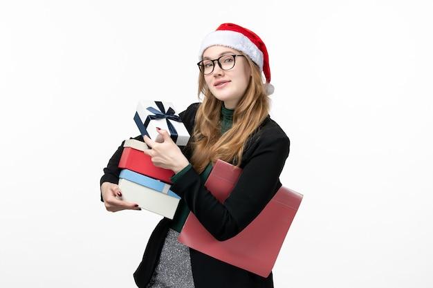 Vorderansicht junge frau, die feiertagsgeschenke auf weißem schreibtischgeschenkbuch-neujahr hält