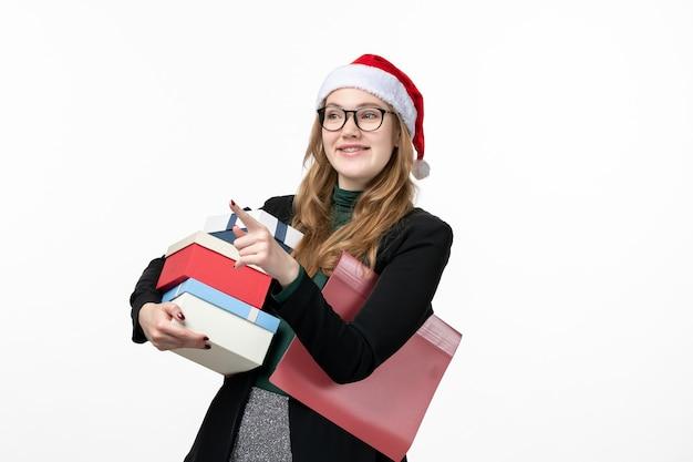 Vorderansicht junge frau, die feiertagsgeschenke auf weißem wandgeschenkbuch neues jahr hält