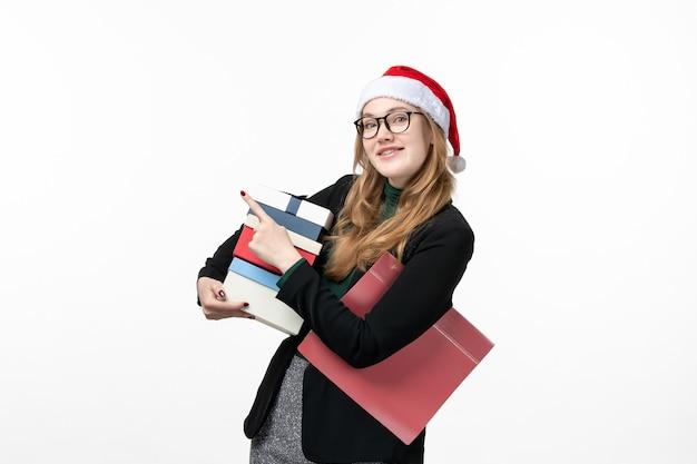 Vorderansicht junge frau, die feiertagsgeschenke auf weißem wandgeschenkweihnachten hält