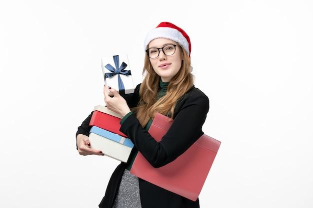 Vorderansicht junge frau, die feiertagsgeschenke auf weißen wandgeschenkbüchern neues jahr hält