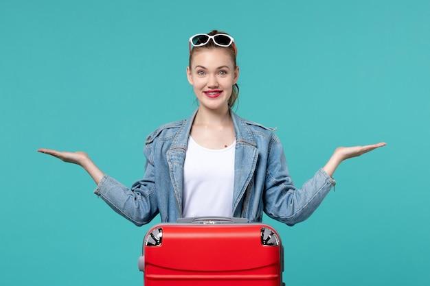 Vorderansicht junge frau, die für reise bereit ist und auf blauem raum lächelt