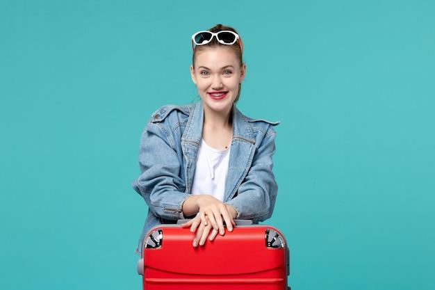 Vorderansicht junge frau, die für reise bereit ist und auf dem blauen raum lacht