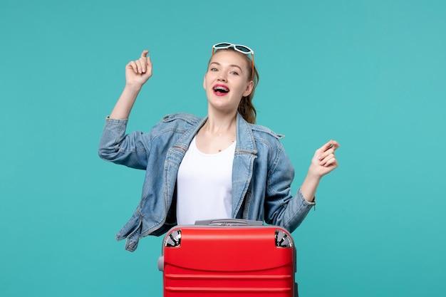 Vorderansicht junge frau, die für reise bereit ist und auf dem blauen raum tanzt