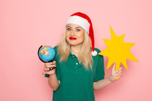 Vorderansicht junge frau, die globus und gelbe figur auf rosa wandmodellfrau-weihnachtsfeiertagsfoto-neujahrsfarbe hält