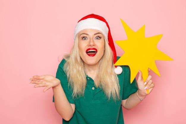 Vorderansicht junge frau, die große gelbe figur auf der rosa wandmodellfrau-weihnachtsfeiertagsfoto-neujahrsfarbe hält